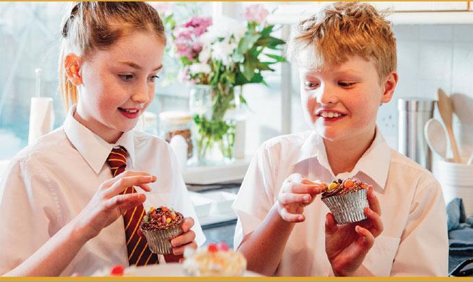 2 school children eating cupcakes