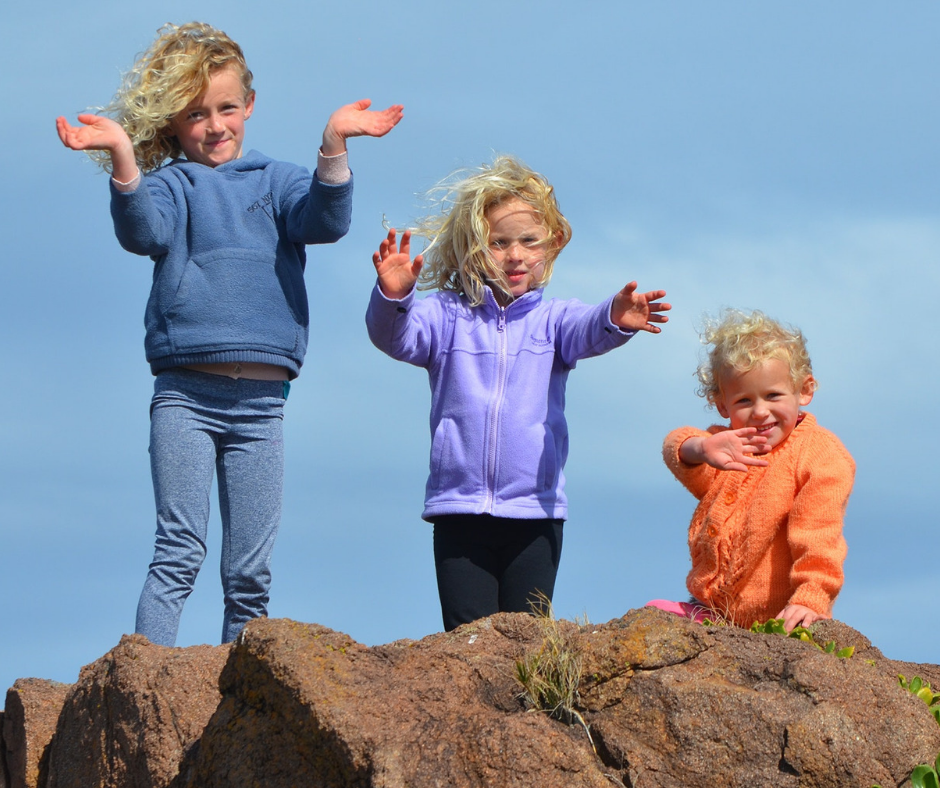 three blonde haired siblings standing next to each other on a rock waving