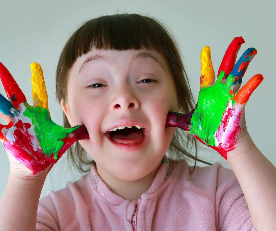 a little girl with downs with her hand painted mulitcolours