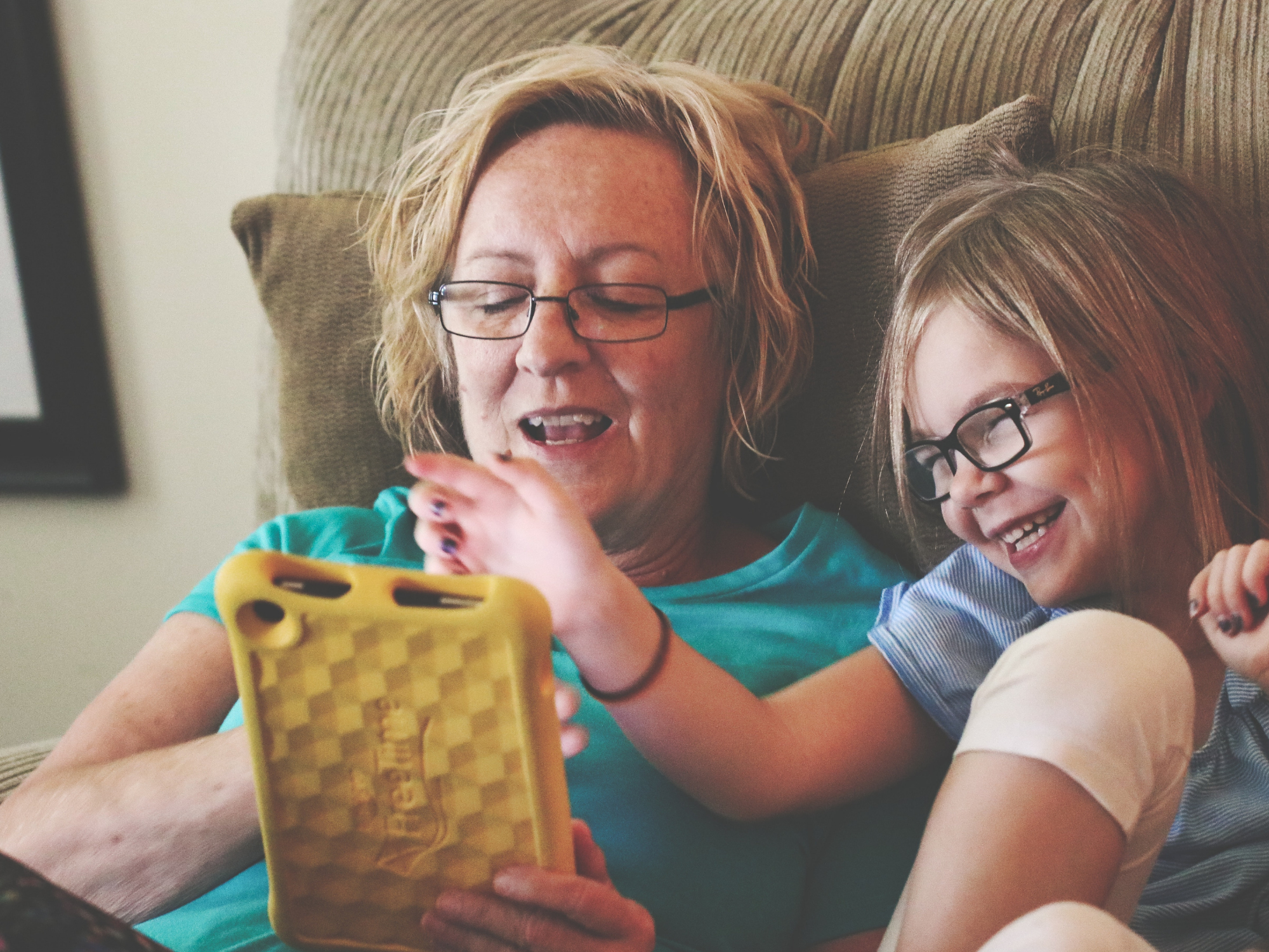 An older lady playing with a young girl on a tablet, both are smiling