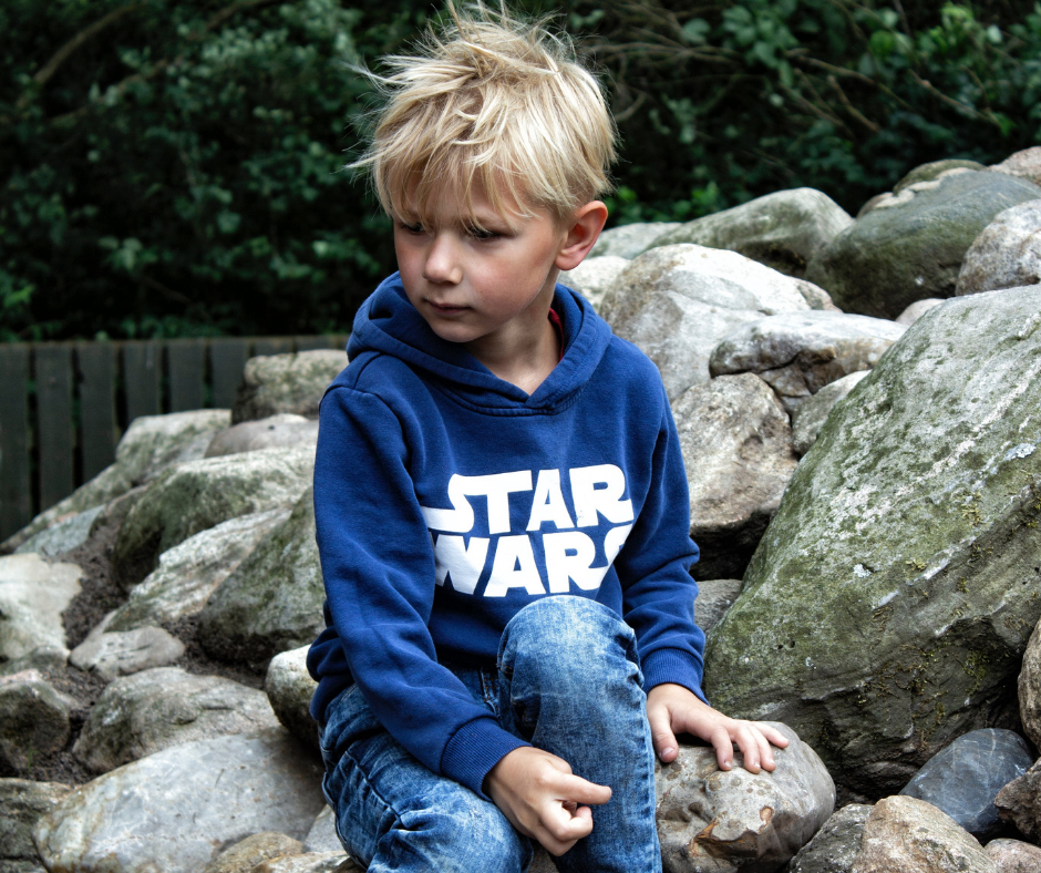 a young boy sat on a rock with a star wars jumper on