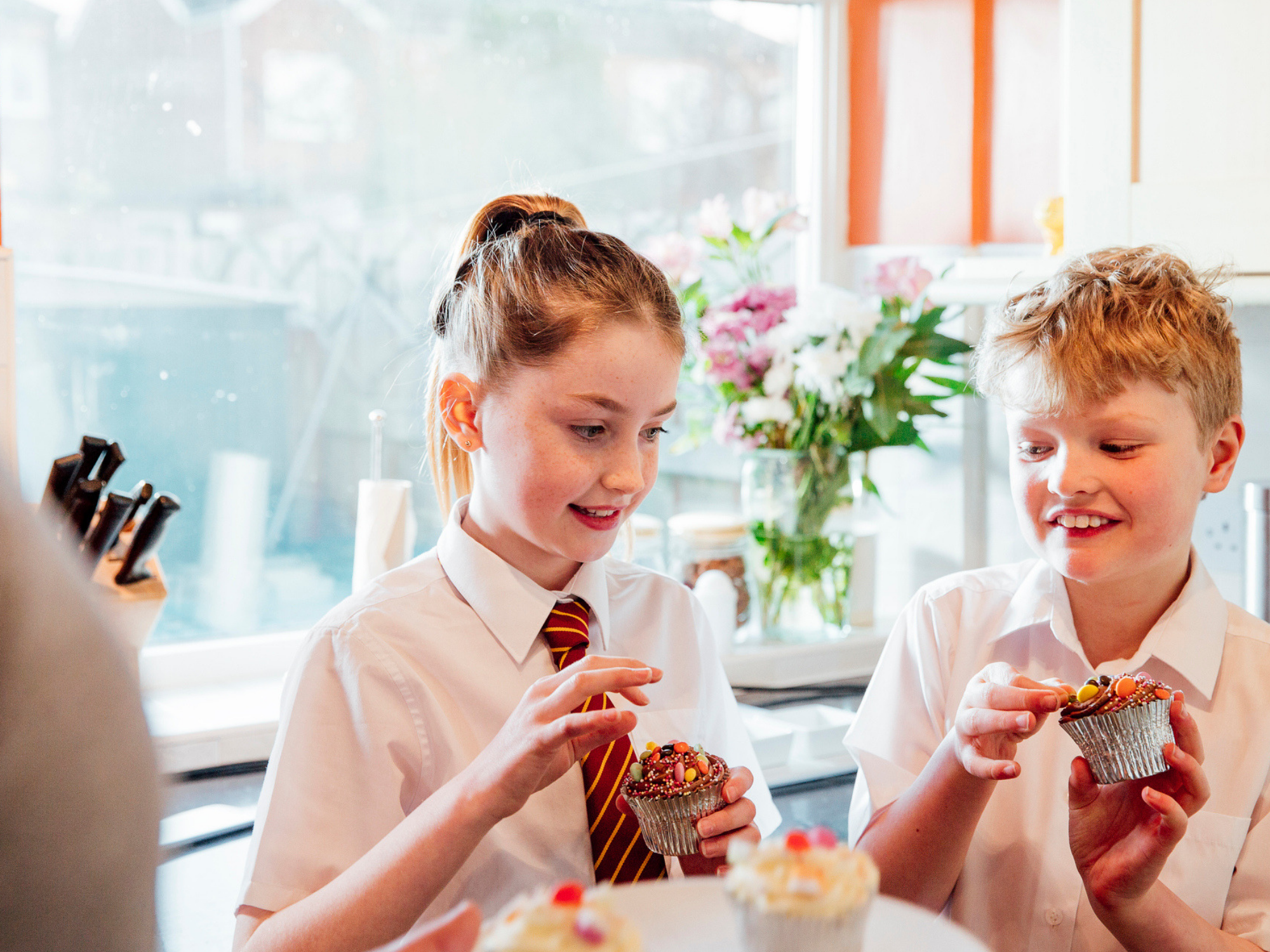 A boy and girl eating cupcakes standing in a kitchen in their school uniforms