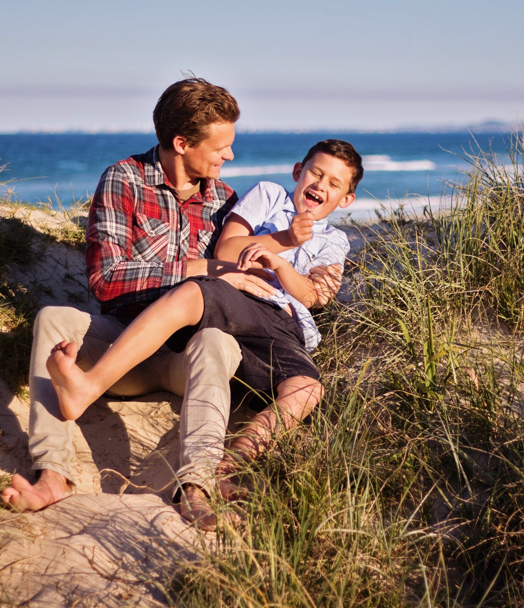 Father and son sitting in sand dunes at the beach, dad is tickling the son who is laughing