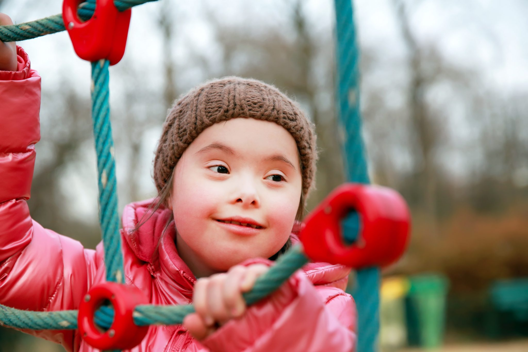 Portrait of beautiful girl with downs syndrome playing in a playground