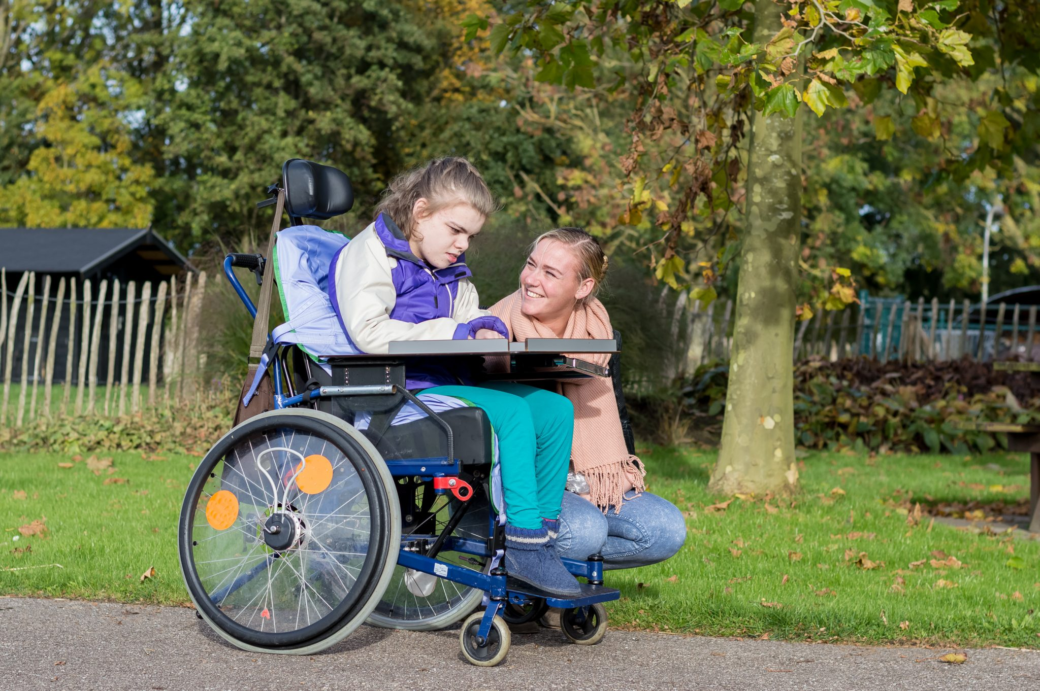 disabled girl in a wheelchair smiling with a woman knelt down next to her