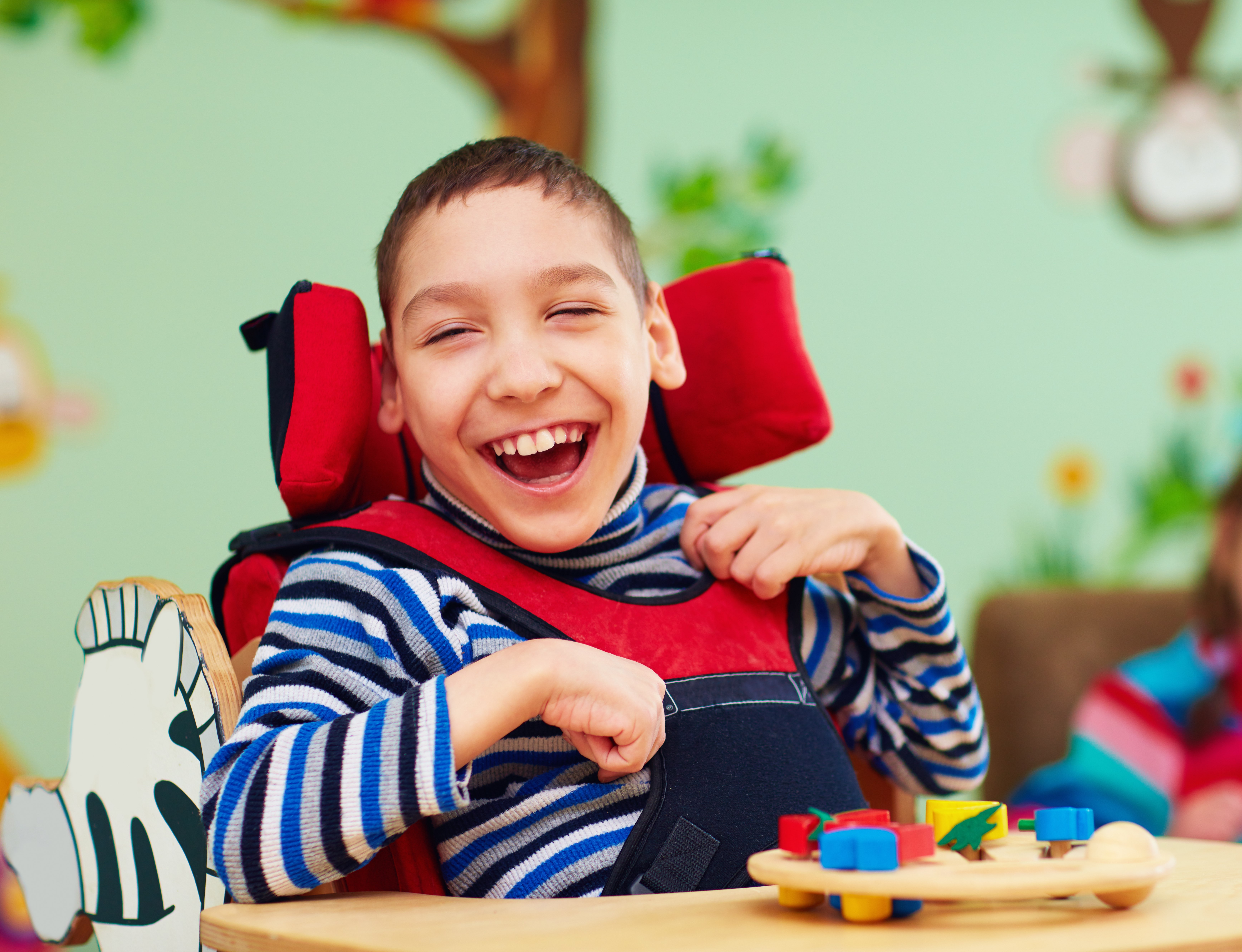 Very happy young boy in a wheelchair grinning for the camera